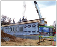 Sullivan Modular--The Affordable Housing Commission assisted with the funding of the Sullivan Place Homes, a single-family, for-sale development built with sustainable practices and materials in the 5th Ward. In this photo, the first energy-efficient modular home is delivered and erected.